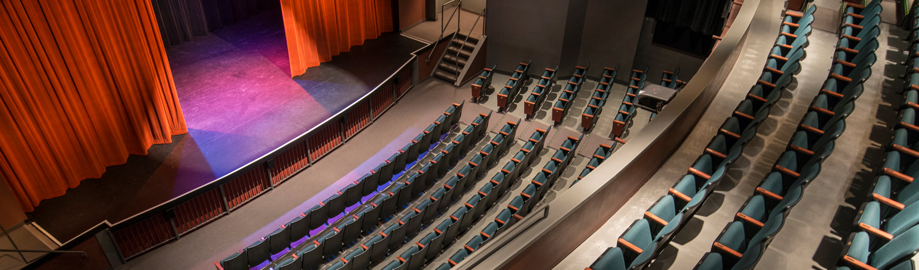 image of theatre from balcony and all of the 401 seats facing a stage with red curtains which are drawn back