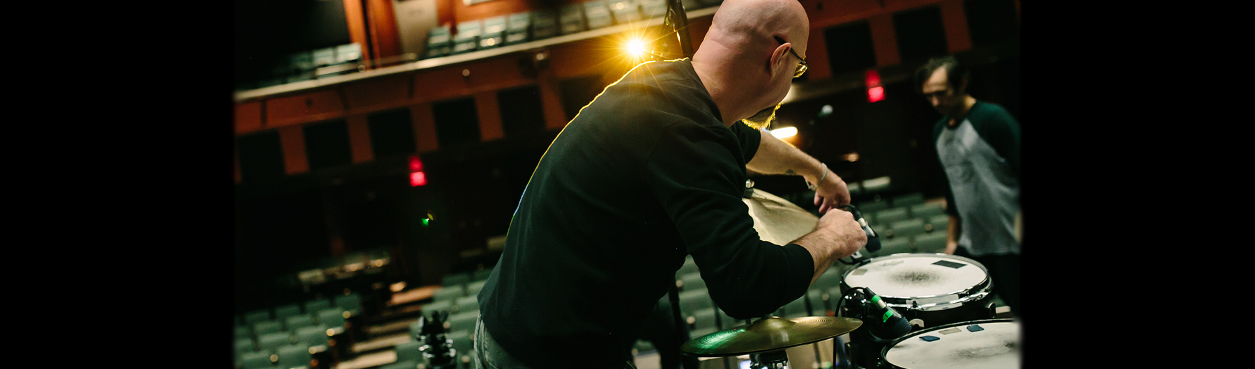 image of theatre crew setting up a drum set on stage, before a show