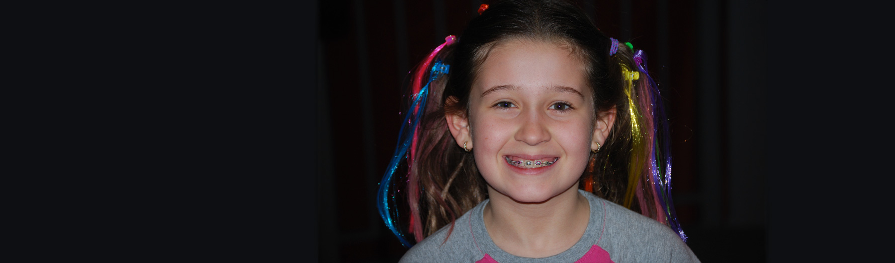 image of a youth smiling with braces, and colourful hair clips