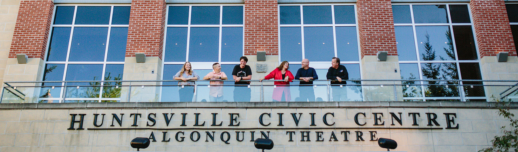 image of theatre staff standing and chatting on the outdoor balcony of the Huntsville Civic Centre Algonquin Theatre